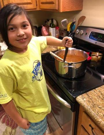 Ella cooking a Food Hero soup recipe